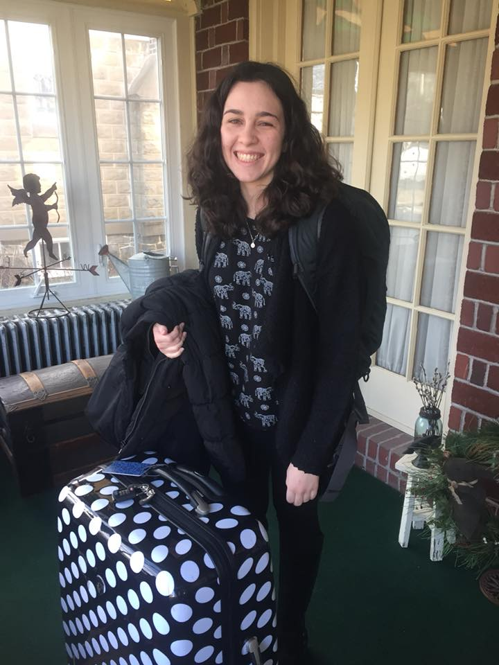 Julianna on the porch with her polka dot suitcase and big backpack, getting ready to leave for her semester abroad.