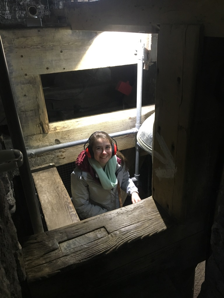 Emily makes her way to the top of the bell tower...with a bell right next to her!  Next step: get onto the wooden beam at the front of the photo. Photo courtesy of Tori Grubb.